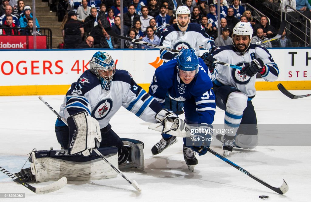 Auston Matthews #34 of the Toronto Maple Leafs tries to get a shot away on Connor Hellebuyck #37 of the Winnipeg Jets as Dustin Byfuglien #33 watches during the first period at the Air Canada Centre on February 21, 2017 in Toronto, Ontario, Canada.