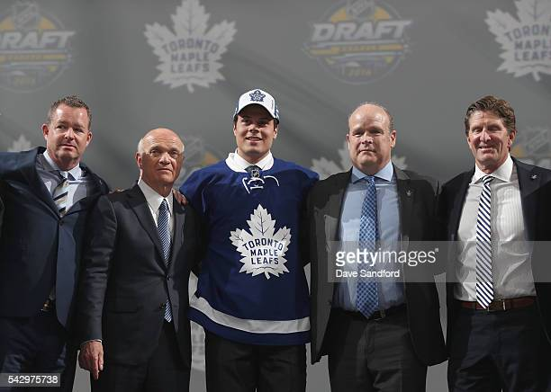 Auston Matthews poses onstage with general manager Lou Lamoriellosecond from left director of player personnel Mark Hunter second from right and head...