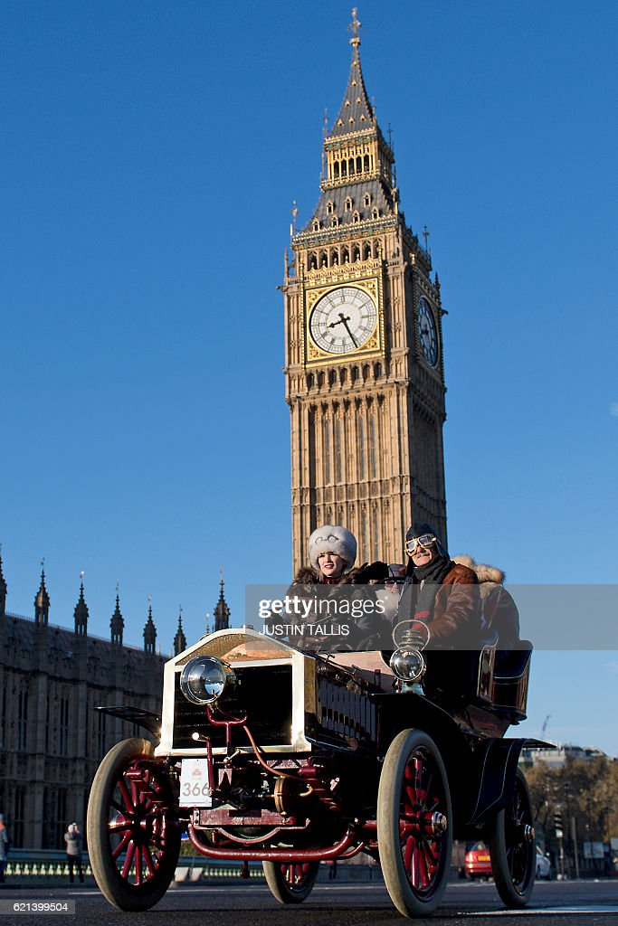 Austra Priede-Klavina (L) drives a 1904 Krastin vintage car past the Houses of Parliament in Westminster shortly after beginning the 120th 'Veteran Car Run' from Hyde Park in London, to Brighton in southern England, on November 6, 2016. Around 600 classic cars took part in the annual 60 mile journey to the south coast resort. / AFP / JUSTIN