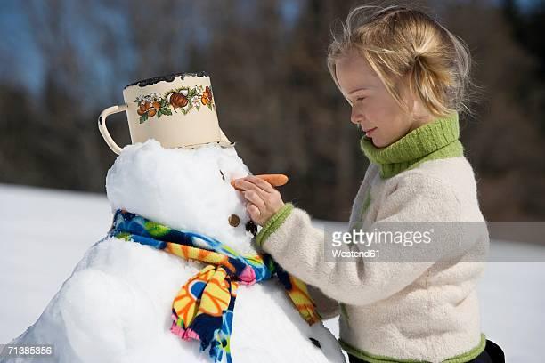 Austrai, girl (6-7) fixing carrot on snowman's face, smiling, portrait