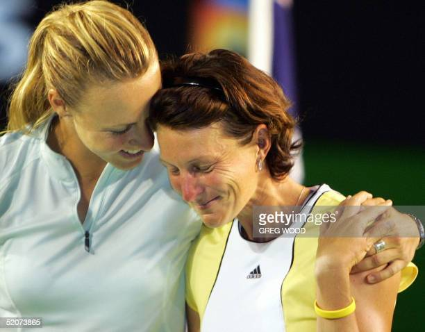 A tearyeyed Corina Morariu of the US receives a hug from Alicia Molik of Australia as the former's partner and compatriot Lindsay Davenport gives a...