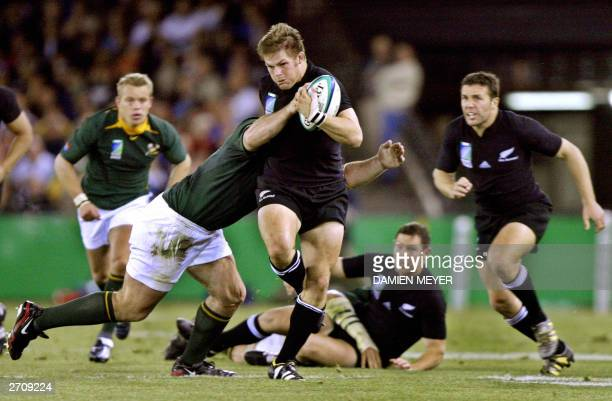 All Blacks flanker Richie McCaw is tackled by an unidentified South African player during the Rugby World Cup quaterfinal match between New Zealand...