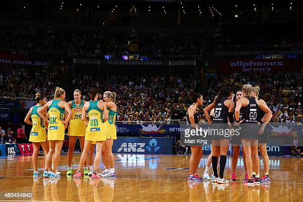 Australia and New Zealand form huddles on court during the 2015 Netball World Cup match between Australia and New Zealand at Allphones Arena on...