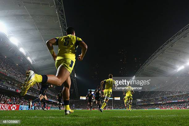 Australia and Spain run onto the field for their Pool B match during day one of the 2014 Hong Kong Sevens at Hong Kong International Stadium on March...