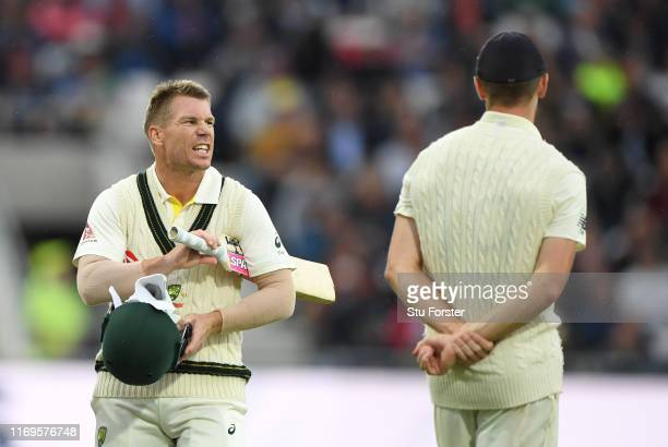 Australia batsman David Warner has a word with England bowler Chris Woakes as players go off for bad light during day one of the 3rd Ashes Test match...