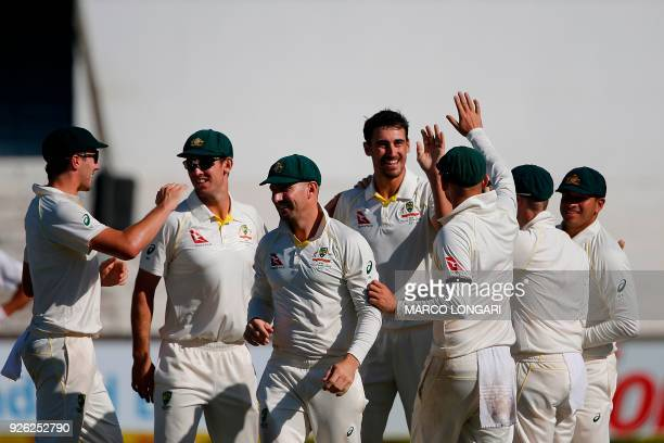 Australia bowler Mitchell Starc celebrates with teammates the wicket of South Africa batsman Faf du Plessis during day two of the first Test cricket...
