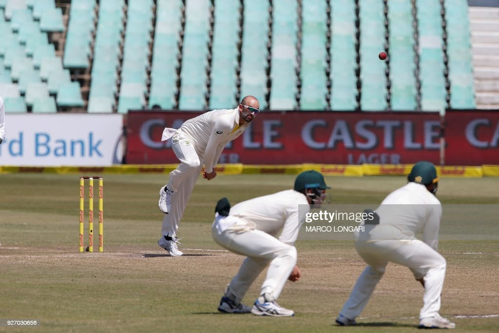 Australia bowler Nathan Lyon (L) delivers the ball to South Africa batsman Theunis de Bruyn (not seen) during the fourth day of the first Test cricket match between South Africa and Australia at The Kingsmead Stadium in Durban on March 4, 2018. /