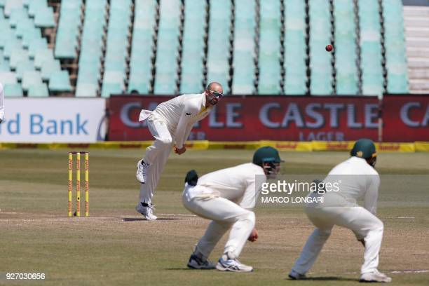Australia bowler Nathan Lyon delivers the ball to South Africa batsman Theunis de Bruyn during the fourth day of the first Test cricket match between...