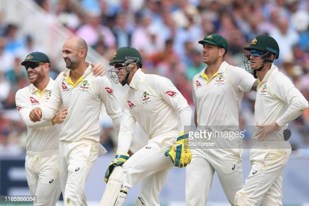 Australia bowler Nathan Lyon is congratulated after bowling England batsman Moeen Ali leaves the field after being bowled for 0 during Day three of...