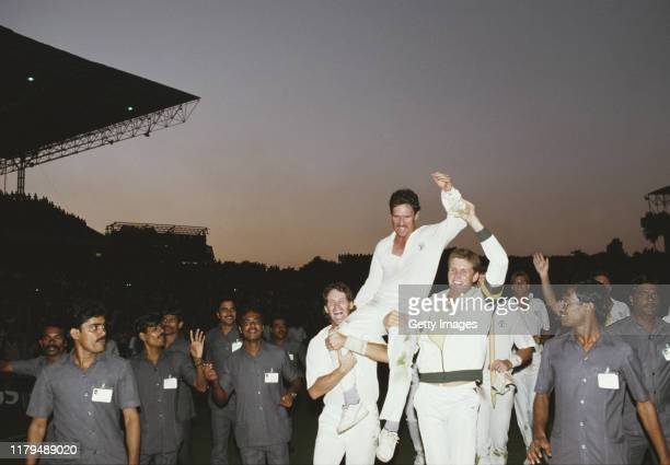 Australia captain Allan Border is hoisted high by team mates Dean Jones and Tom Moody as local security guards follow round after Australia had...