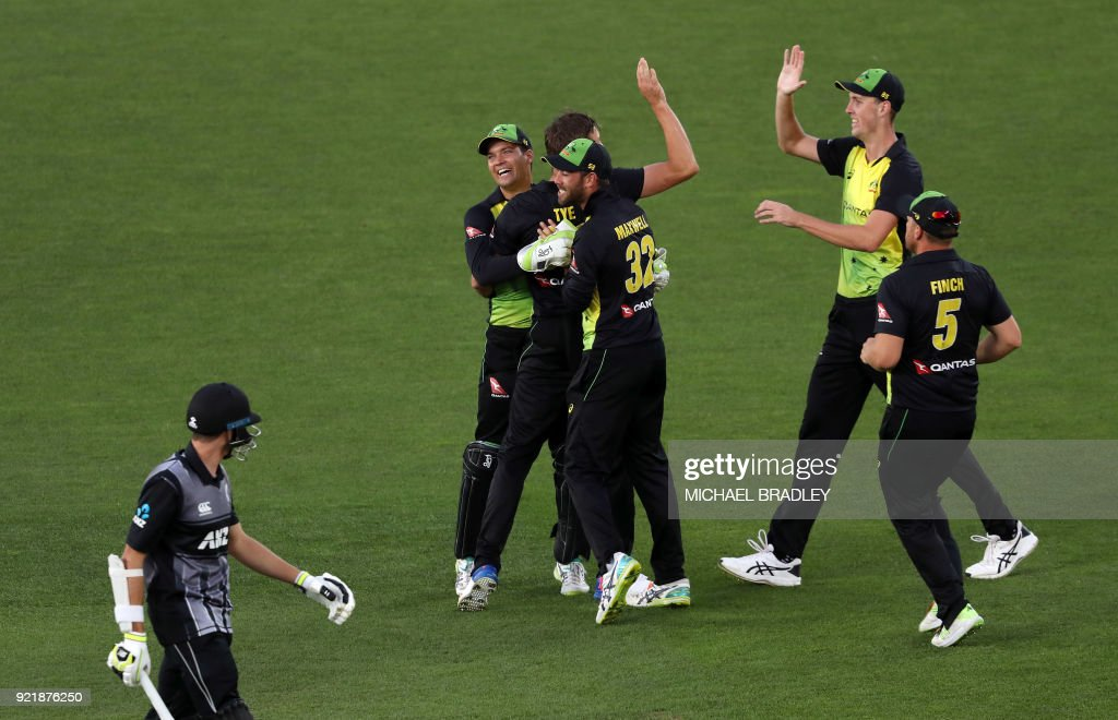 Australia celebrate taking the wicket of New Zealand's Mitchell Santner (bottom L) during the final Twenty20 Tri Series international cricket match between New Zealand and Australia at Eden Park in Auckland on February 21, 2018. /