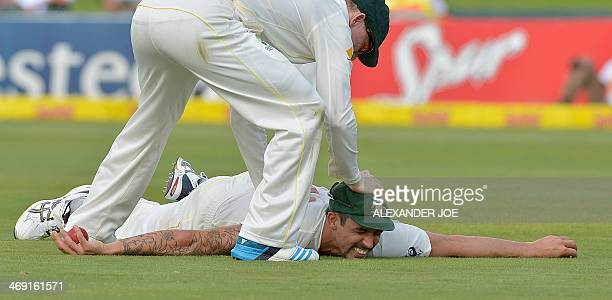 Australia cricketer Mitchell Johnson is congratulated by an unidentified teammate after catching out unseen South Africa's cricketer JP Duminy for 25...