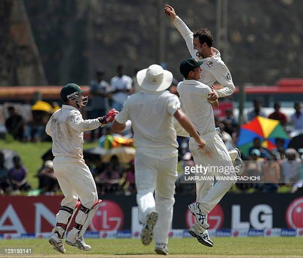 Australia cricketer Nathan Lyon celebrates with his teammates after he dismissed unseen Sri Lankan batsman Chanaka Welegedara during the second day...
