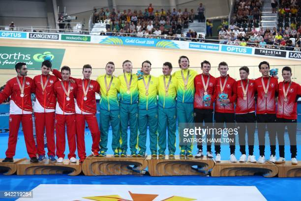 Australia England and Canada teams pose on the podium for their respective gold silver and bronze medal wins in the men's 4000m team pursuit finals...
