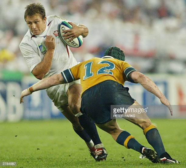 English flyhalf Jonny Wilkinson is tackled by Wallaby centre Elton Flatley during the Rugby World Cup final between Australia and England at the...