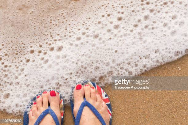 australia flag thongs or flip-flops on an australian beach with sea foam touching the thongs and toes. - australia day stock pictures, royalty-free photos & images