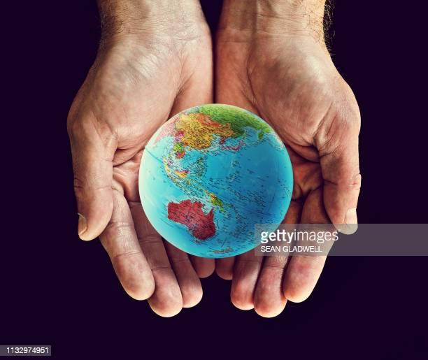 australia globe hands - europa kontinent stock-fotos und bilder