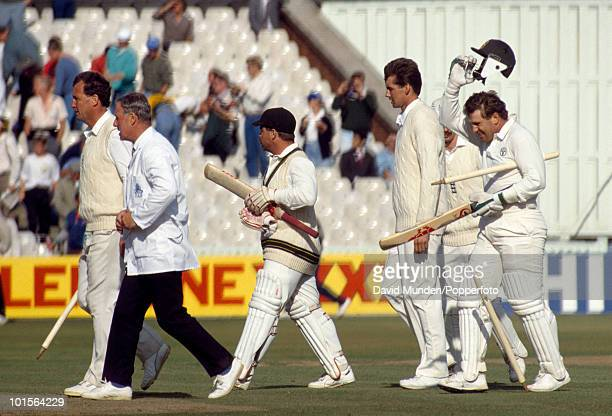 Australia have regained the Ashes and batsman Mark Taylor raises his helmet in celebration as he leaves the field at the end of the 4th Test match...