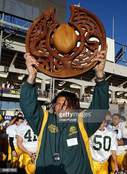 Australia Head Coach John Roe holds the trophy after Australia's win in the American Football match between the New Zealand Iron Blacks and Australia...