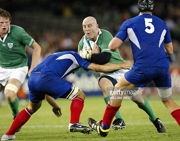 Irish hooker and captain Keith Wood is tackled by French lock Jerome Thion and French lock Fabien Pelous during Rugby World Cup quarterfinal match...