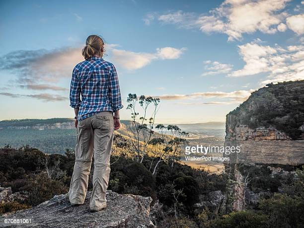 australia, new south wales, blue mountains, blackheath, megalong valley, mature woman standing on rock and looking at valley below - great dividing range stock-fotos und bilder