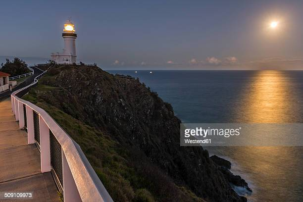 Australia, New South Wales, Byron Bay, Cape Byron Bay lighthouse and full moon over the sea after dusk