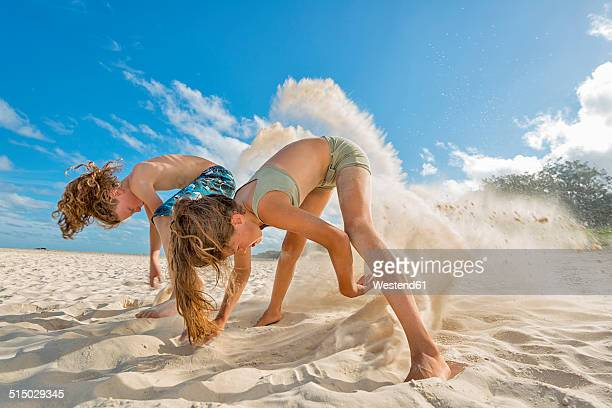 australia, new south wales, pottsville, boy and girl digging in sand on beach - little girls bent over stock photos and pictures