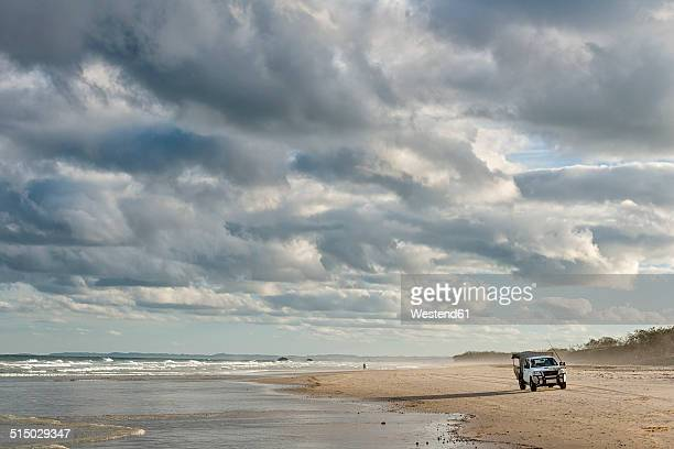 Australia, New South Wales, Pottsville, off-road vehicle standing on beach with surf and dark clouds