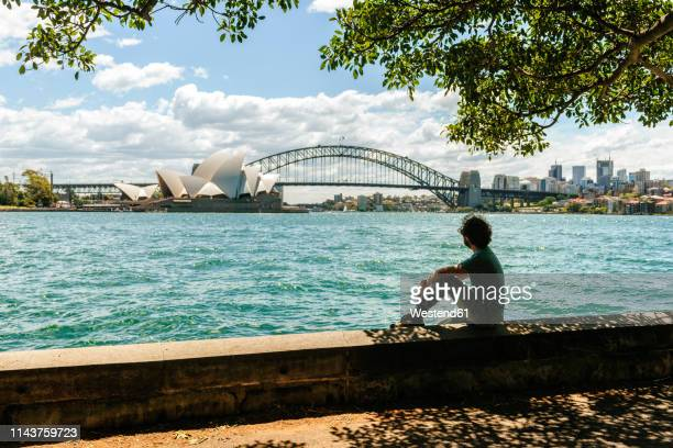 australia, new south wales, sydney, man looking towards the bridge and the sydney opera house - sydney stock pictures, royalty-free photos & images