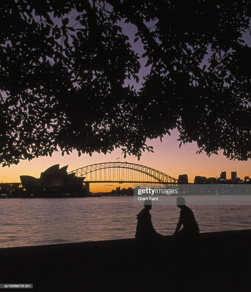 Australia, New South Wales, Sydney, silhouette of couple with Harbour Bridge and Opera house in background at sunset : Stockfoto