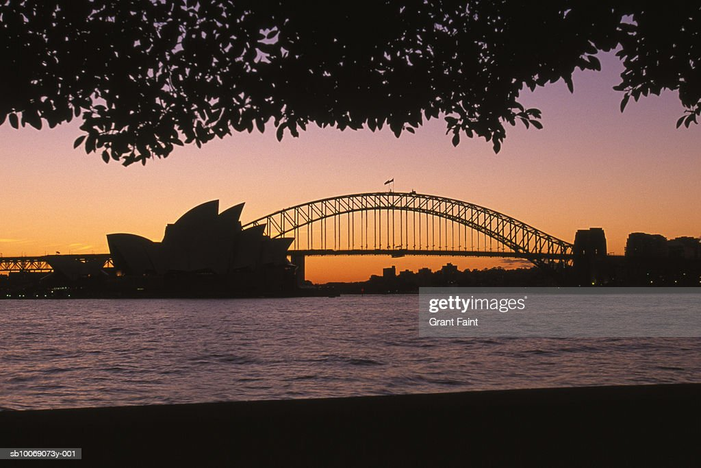 Australia, New South Wales, Sydney, silhouette of Opera House and Sydney Harbour Bridge at sunset : Stockfoto