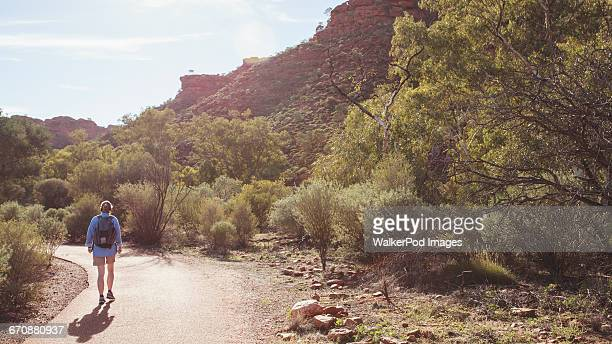 Australia, Outback, Northern Territory, Red Centre, West Macdonnel Ranges, Kings Canyon, Woman walking down mountain road