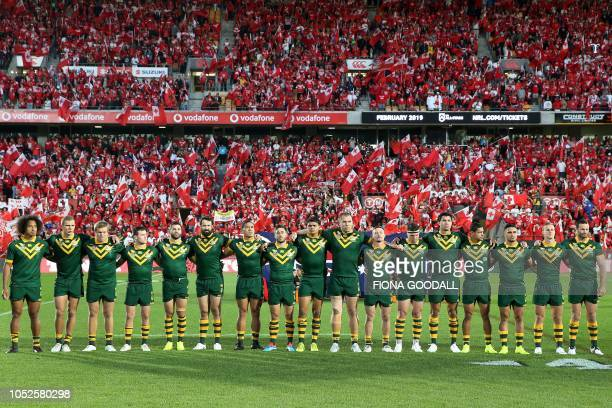 Australia players sing the national anthem with a backdrop of red prior to the rugby league international Test match between Australia and Tonga at...