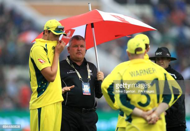 Australia players speak to the 4th Umpire as they leave the pitch because of rain during the ICC Champions Trophy Group A match at Edgbaston...