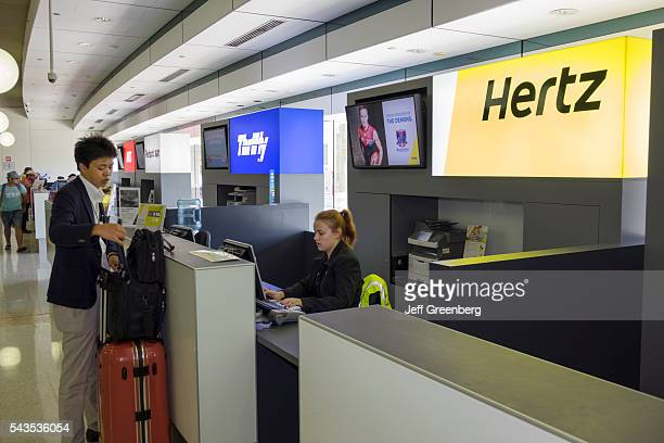 Australia Queensland Brisbane Brisbane Airport BNE terminal concourse car rental counter Hertz Thrifty competing businesses Asian man customer woman...