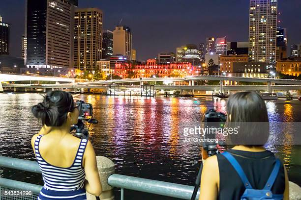 Australia Queensland Brisbane Central Business District city skyline skyscrapers buildings night nightlife Southbank Asian woman photographer tripod...