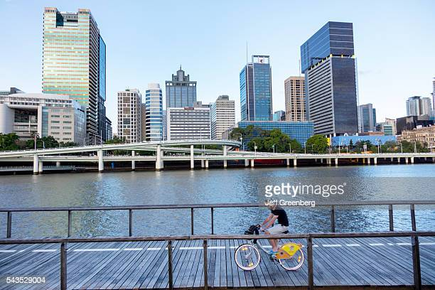 Australia Queensland Brisbane Central Business District Victoria Bridge Southbank city skyline skyscrapers buildings man bicycle riding City Cycle...