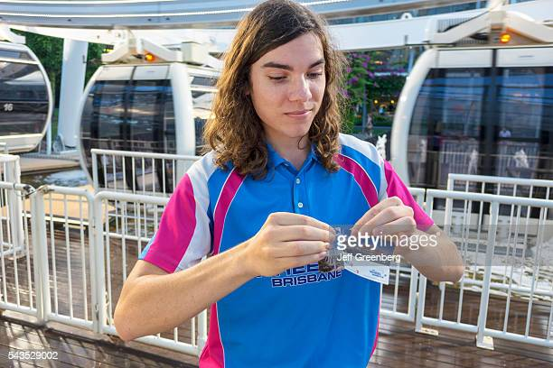 Australia Queensland Brisbane Southbank The Wheel Ferris wheel teen boy job tearing ticket ride long hair