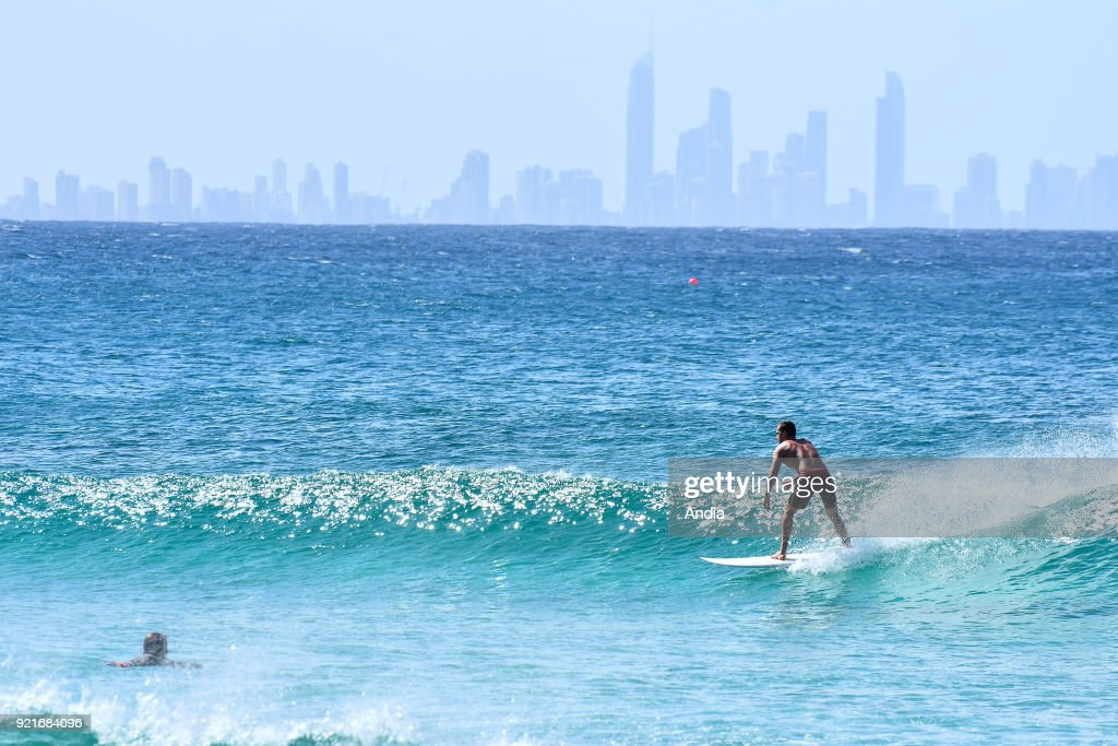 Rainbow beach, surfer on a wave and buildings of the Gold Coast in the background, southern Queensland.
