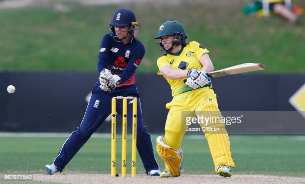 Australia 's Alex Blackwell hits a shot as Sarah Taylor looks on during the Women's International One Day match between Australia and England on...