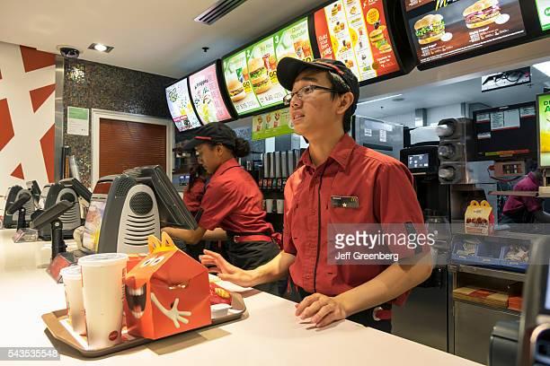 Australia, Sydney, CBD Central Business District Circular Quay McDonald's restaurant fast food counter ordering Asian man job employee tray serving...