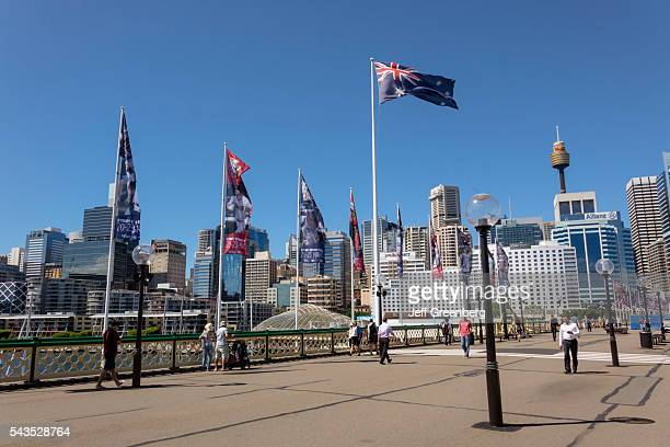 Australia Sydney Central Business District CBD Darling Harbor Pyrmont Bridge pedestrian walking Cockle Bay skyscrapers city skyline flag Sydney Tower