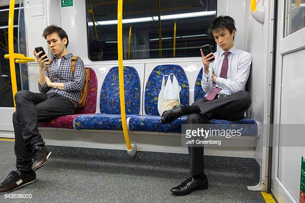 Australia Sydney Trains City Circle public transportation onboard cabin riders passengers Asian man looking smartphone messages commuters