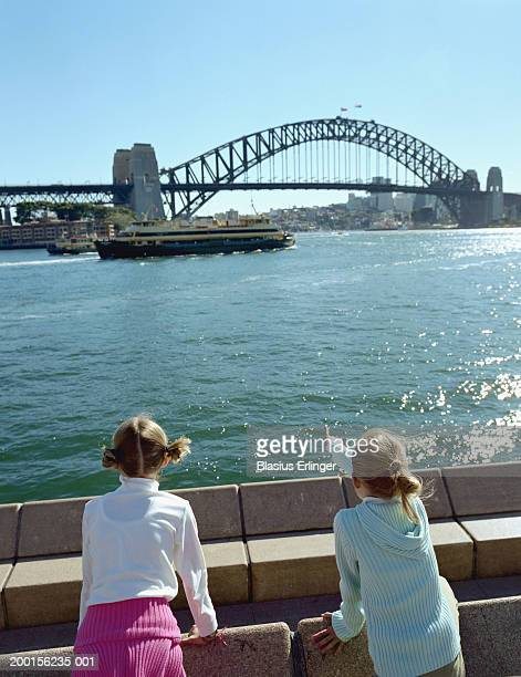 australia, sydney, two girls (9-11) looking at harbor, rear view - blasius erlinger stock pictures, royalty-free photos & images