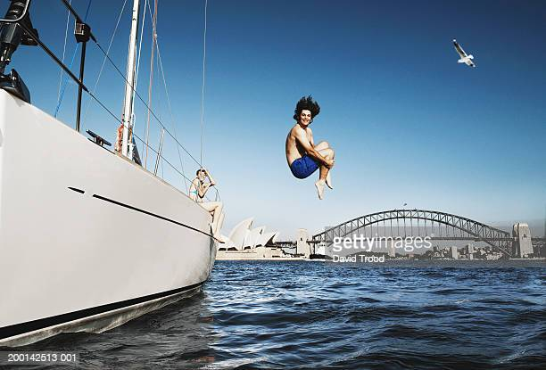 australia, sydney, young man jumping from boat in to harbour - sydney stock pictures, royalty-free photos & images