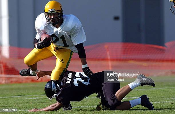 Australia Tail back Desi Duguid gets out of the tackle of Ricky Penu during the American Football match between the New Zealand Iron Blacks and...