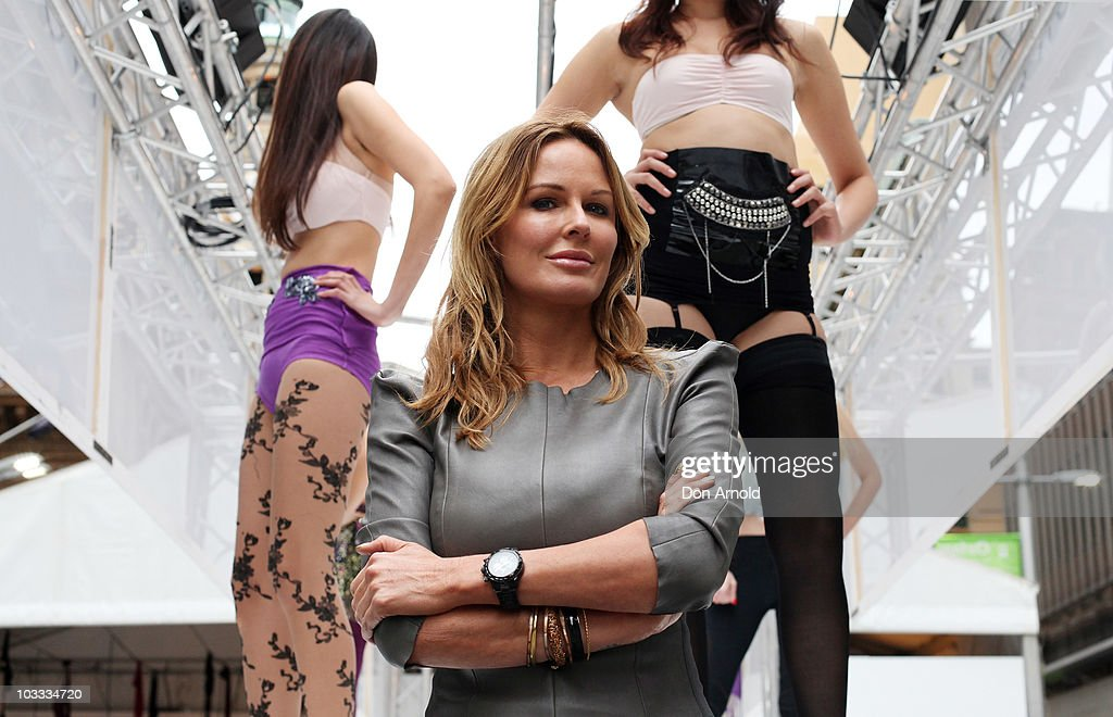 Australia television personality Charlotte Dawson poses in front of models showcasing designs by Voodoo Hosiery on the catwalk at a media preview of a 'topless' runway show at Martin Place on August 11, 2010 in Sydney, Australia.