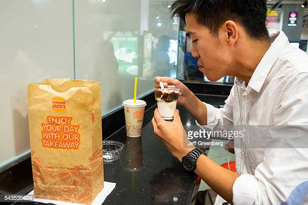 Australia Victoria Melbourne Central Business District CBD Central Station Hungry Jack's Burger King fast food restaurant Asian man ice cream bag...