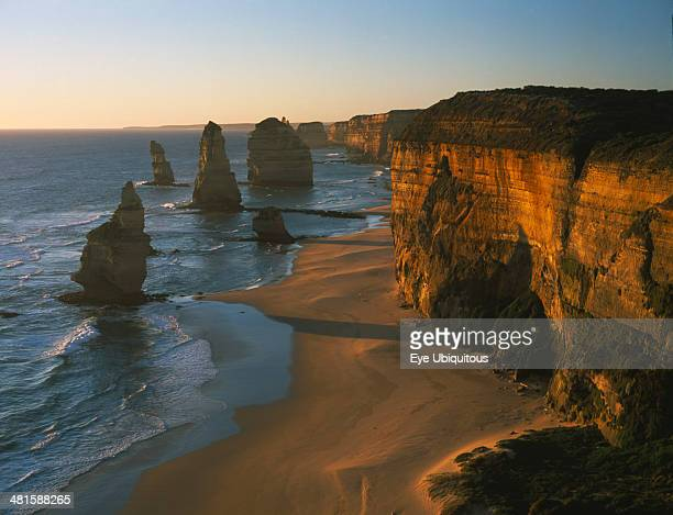 Australia Victoria Port Campbell NP Great Ocean Road View along the beach and cliffs toward The Twelve Apostles sea stacks in warm evening light