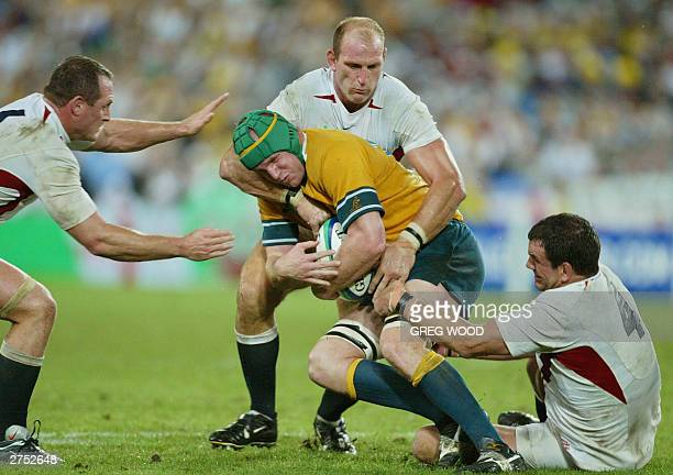 Wallaby number 8 David Lyons is tackled by English number 8 Lawrence Dallaglio and English captain and lock Martin Johnson during the Rugby World Cup...